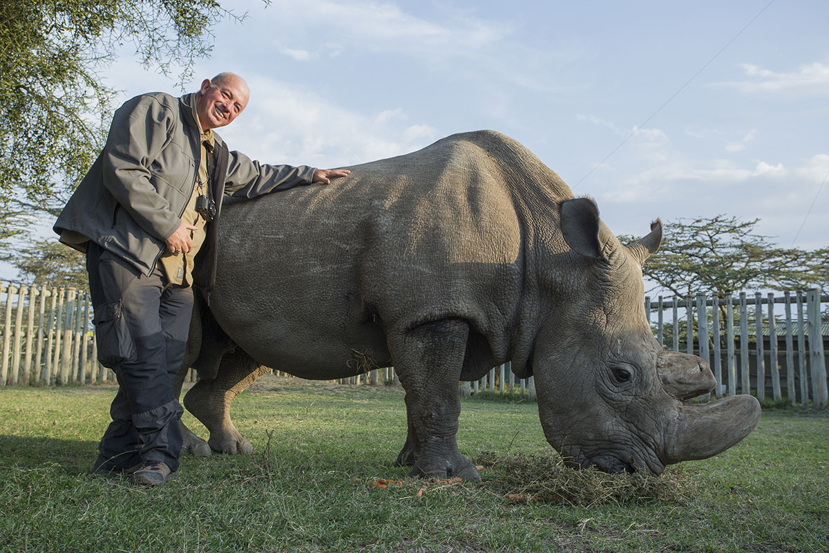 Image shows Chris Galvin with Sudan, the last male Northern White Rhinoceros